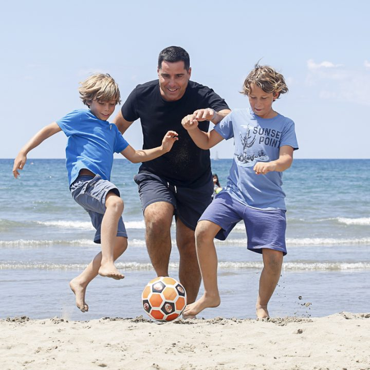 Riccardo Silva playing football with his sons at the beach